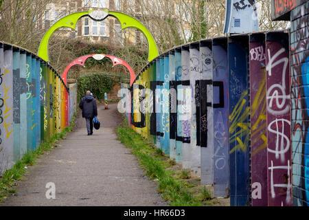 Un hombre camina a través de una pasarela sobre una línea férrea en Montpelier, Bristol, que está Imagen De Stock