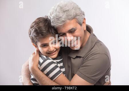Abuelo y nieto abrazándose entre otros Imagen De Stock