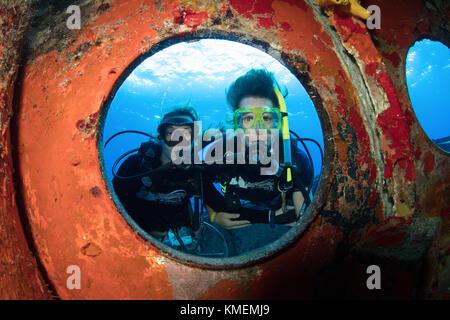 Los buceadores peer a través de ojo de buey en uss kittiwake. Imagen De Stock