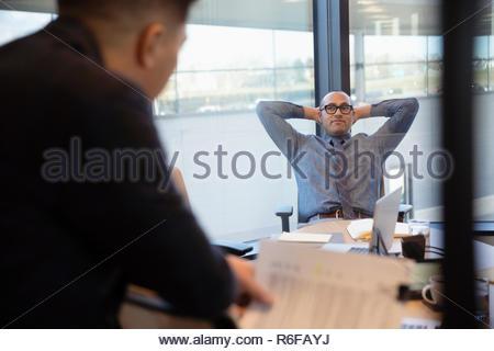 Empresario con las manos detrás de la cabeza en la sala reunión Imagen De Stock