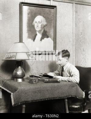 1930 ESTUDIOSO haciendo los deberes sentado leyendo en la mesa bajo el retrato DE GEORGE WASHINGTON - s8901 HAR001 HARS MENORES ESTUDIOSO Lámpara de mesa blanco y negro la etnia CAUCÁSICA HAR001 ANTICUADO Imagen De Stock