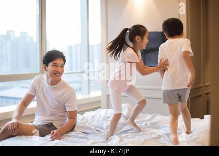 Joven alegre familia divirtiéndose en una cama Imagen De Stock