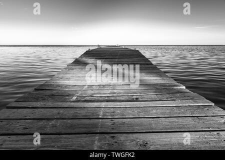 Cortar sombras a través de embarcadero de madera al atardecer en impresionante blanco y negro Imagen De Stock