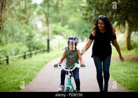 Feliz madre hija enseñando cómo correr en bicicleta Imagen De Stock