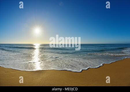Olas rompiendo en la orilla de la Playa de las 90 millas de playa Paraíso con el sol brillando sobre el océano en Victoria, Australia Imagen De Stock
