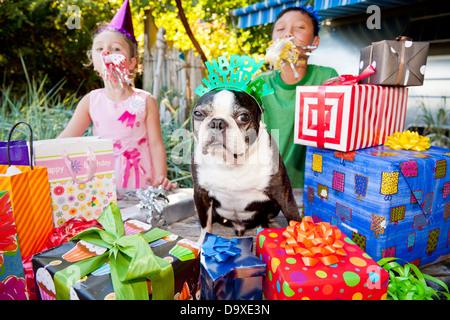 Dos niños y un perro en la fiesta de cumpleaños al aire libre Imagen De Stock