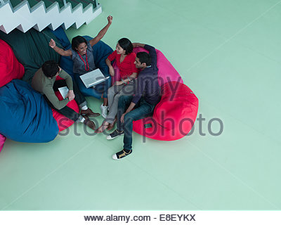 Gente de negocios entusiasmados con los brazos levantados sentados en sillas y bean bag mirando portátil Imagen De Stock