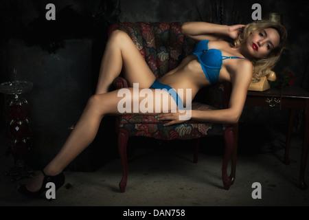 Reclinable joven rubia sexy mujer en azul bra Lencería y ropa interior en una silla. Imagen De Stock