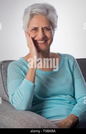 Retrato de altos mujer sonriente sentado en un sofá con la mano Imagen De Stock