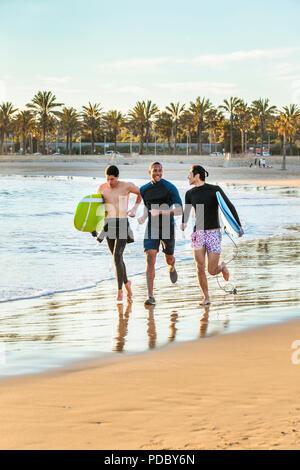 Entusiasta surfista masculino corriendo con tablas de surf en la playa. Imagen De Stock