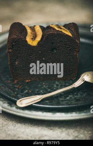 Pieza de chocolate recién horneadas torta de pan de banano postre sobre placa de hormigón gris de fondo de la tabla, el enfoque selectivo Imagen De Stock
