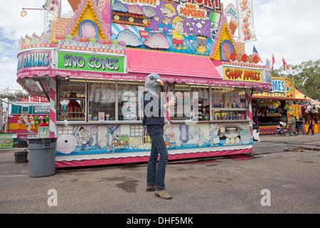 Mujer vistiendo una máscara paloma posee una pata de pavo en la feria estatal. Imagen De Stock
