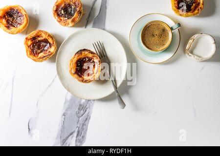 Tarta de huevo tradicional portuguesa Pasteis postre Pastel de nata con una taza de café negro y la jarra de leche sobre fondo de mármol blanco. Espacio laical, plana Imagen De Stock