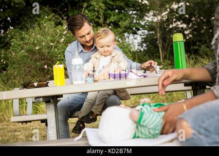 Padre sentado con mi hijo (18-23 meses) por mesa de picnic Imagen De Stock