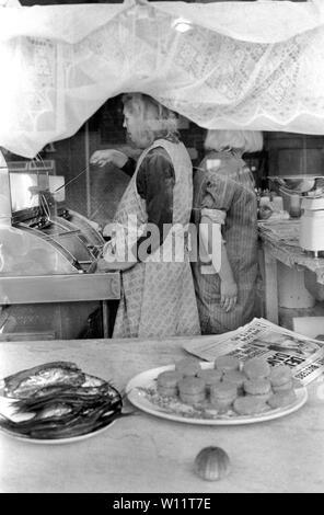 Fish and Chips escaparate dos mujeres trabajando la fritura de pescado, patatas fritas y sirviendo de Northumberland UK 1970. HOMER SYKES Imagen De Stock