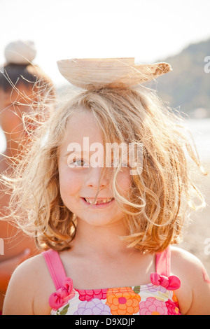 Joven equilibrio concha grande sobre su cabeza Imagen De Stock