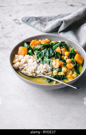 La calabaza, garbanzo, arroz con curry y espinacas. Imagen De Stock