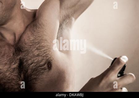 Foto de estudio de mediados de hombre adulto pulverizando desodorante Imagen De Stock