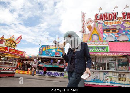 Mujer vistiendo una máscara de la paloma se encuentra en un carnaval comiendo una pata de pavo. Imagen De Stock