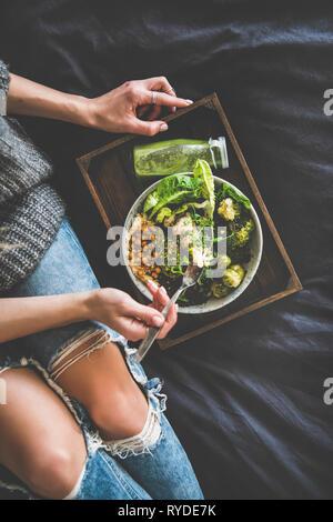 Cena saludable, comer en la cama. Superbowl vegano o Buda bowl con hummus, ensaladas, verduras, frijoles, cuscús y aguacate, batido en una bandeja y wo Imagen De Stock