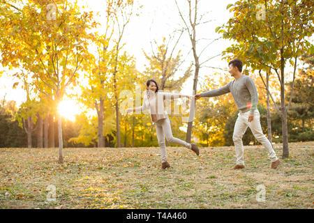 Joven pareja feliz corriendo en otoño woods Imagen De Stock