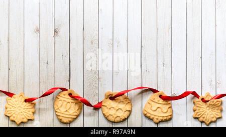 Borde de la Navidad en forma de cookies roscado en cinta roja junto a un fondo de madera. Imagen De Stock