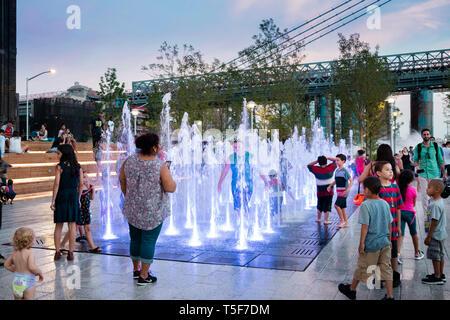 Niños jugando en la fuente. Domino Park, Brooklyn, Estados Unidos. Arquitecto: James Corner Field Operations, 2018. Imagen De Stock