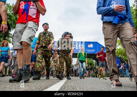 Un soldado cruza la línea de meta mientras diciendo hola a la cámara durante el primer día.Ya que es el más grande del mundo multi-día caminando, el evento de cuatro días de marzo es visto como el primer ejemplo de deportividad y pegado internacional entre militares y civiles y de las mujeres de muchos países diferentes. Los participantes en la 103ª comenzaron los cuatro días marchas en Nijmegen, en la Wadren a las 4am, cruzaron el puente Waalbrug (la legendaria de Nijmegen), y pasando por la ciudad de Elst (el día), donde el color oficial era azul. El día era frío, con temperaturas inferiores a Imagen De Stock
