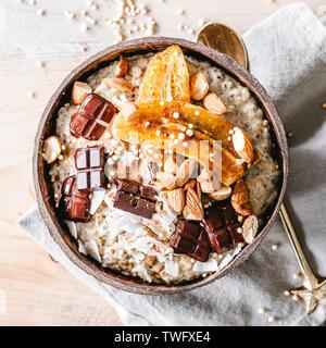 Tazón de avena cubierto con plátano caramelizado, almendras y chocolate Imagen De Stock
