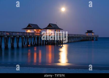 Ajuste la Luna Llena y el crepúsculo matutino sobre el muelle de Nápoles, Naples, Florida, EE.UU. Imagen De Stock