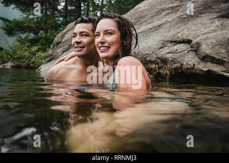 Afectuosa pareja joven nadar en el lago Imagen De Stock