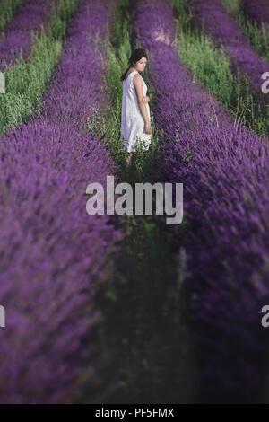 Una niña en un vestido blanco de pie en un campo lila en Provence, Francia Imagen De Stock