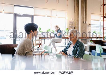 Madre e hija comer y conversar en el café Imagen De Stock