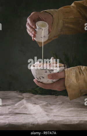 Taza de cerámica de chocolate caliente con malvavisco s'mores en manos femeninas. Verter la crema de la jarra. Mantel de lino de color gris. Bebida de invierno. Atmósfera oscura. Imagen De Stock