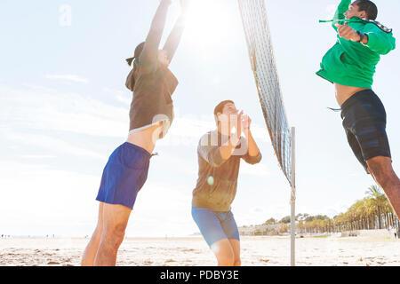 Hombres jugando voleibol de playa en sunny beach Imagen De Stock
