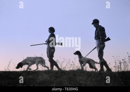 1920 1930 silueta anónima al hombre y a la mujer los cazadores que portan armas, cada uno con un perro de caza - s2541c har001 HARS SILUETAS DE OCIO Y RECREO CANINOS POOCH Conexión anónima COOPERACIÓN CANINA ARMA ARMAS DE FUEGO CAZADORES mamífero adulto medio hombre adulto medio Mediados de-MUJER ADULTA COMPAÑERISMO EN BLANCO Y NEGRO HAR001 ANTICUADO Imagen De Stock