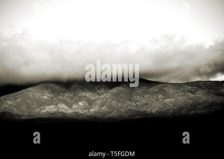 Las nubes y la niebla tire sobre los picos y las crestas de una montaña o una cordillera. Imagen De Stock