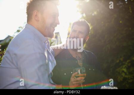 Una pareja gay masculina afectuoso bebiendo vino en el soleado jardín Imagen De Stock