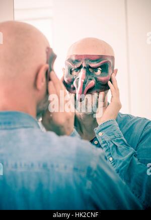 Old Man cubren la cara con la máscara de carnaval. Mirando a sí mismo en un espejo. Concepto de envejecimiento, Imagen De Stock