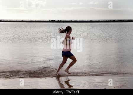 Mujer corriendo en la playa, Tenerife, Islas Canarias, España Imagen De Stock