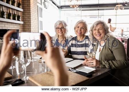 Senior sonrientes mujeres amigas posando para fotografía en restaurante. Imagen De Stock