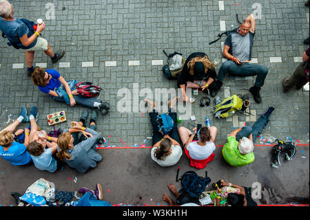 Un grupo de participantes a tomar algún descanso en el suelo durante el primer día.Ya que es el más grande del mundo multi-día caminando, el evento de cuatro días de marzo es visto como el primer ejemplo de deportividad y pegado internacional entre militares y civiles y de las mujeres de muchos países diferentes. Los participantes en la 103ª comenzaron los cuatro días marchas en Nijmegen, en la Wadren a las 4am, cruzaron el puente Waalbrug (la legendaria de Nijmegen), y pasando por la ciudad de Elst (el día), donde el color oficial era azul. El día era frío, con temperaturas inferiores a las de otros años Imagen De Stock