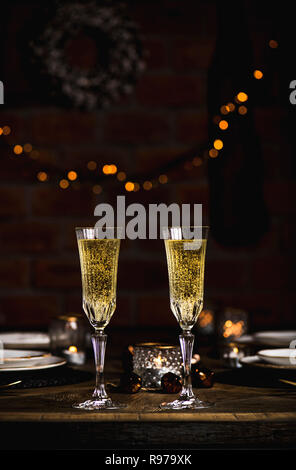 Navidad o Año Nuevo festivo vintage bonita mesa de madera con copas de champán, vajillas, velas y decoración, juguetes, Navidad wreat Imagen De Stock