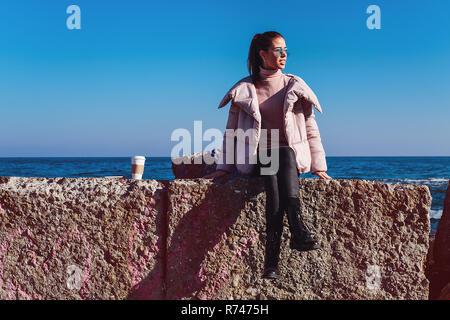 Elegante mujer adulta media sentado en la escollera, Odessa, Odeska Oblast, Ucrania Imagen De Stock