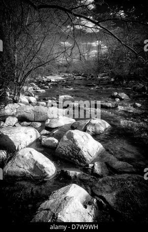 Imagen en blanco y negro de un pequeño arroyo, apresurándose fluye alrededor de grandes piedras en el Imagen De Stock