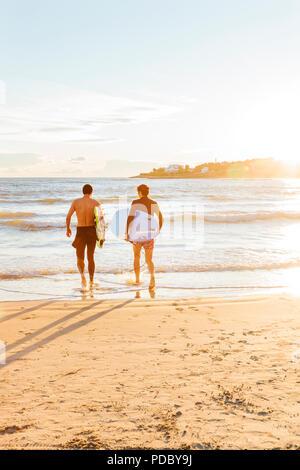 Surfistas masculinos llevar tablas de surf en el océano en sunny beach Imagen De Stock
