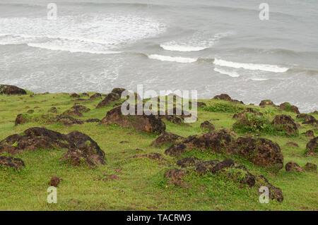SSK - 35216 Un paisaje del mar Arábigo fresco con exuberantes prados verdes de monzón con rocas del fondo y las aguas y las olas en el oriente en el fondo formando un paisaje muy abstracta Ganpatipule Maharashtra India Asia el 26 de septiembre de 2014 Imagen De Stock