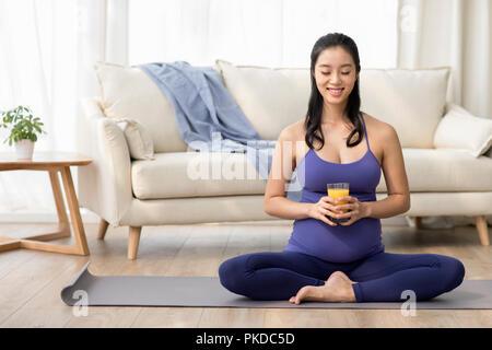 Alegre mujer embarazada sosteniendo un vaso de zumo Imagen De Stock