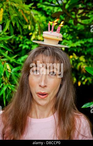 Mujer con cupcake de cumpleaños en la cabeza. Imagen De Stock