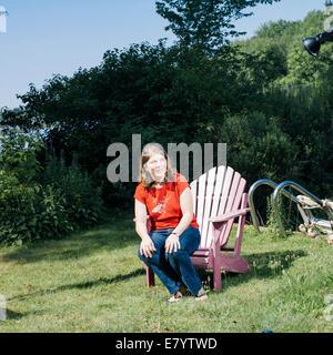 Mujer sentada en el borde de la silla de madera sobre el césped Imagen De Stock
